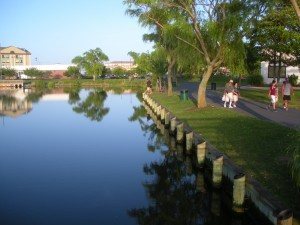 A calm lake bordering a park with trees and grass
