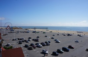 A parking lot right next to the ocean with cars parked on it