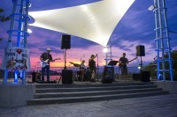 A musical group playing on a concrete stage at night