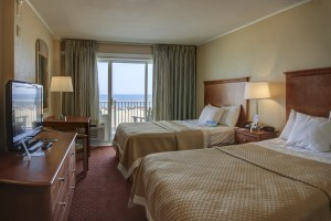 A hotel room overlooking the beach with 2 queen size beds