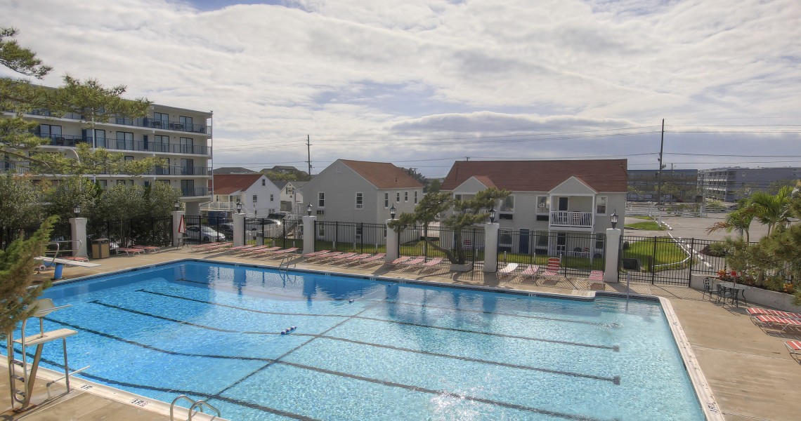 A large outdoor swimming pool next to some condominiums and a hotel