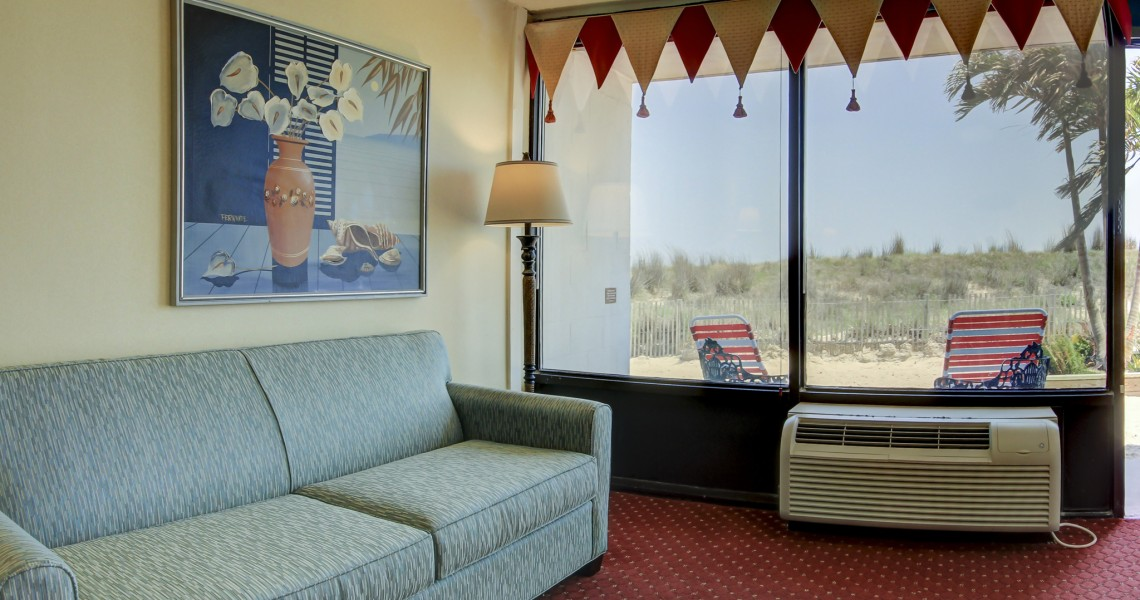 A couch on red carpeting with air conditioning next to the beach