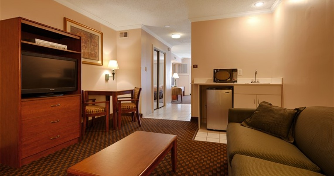 A hotel room with couch, microwave and more