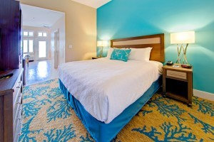 A Half carpeted half tiled room with a King sized bed