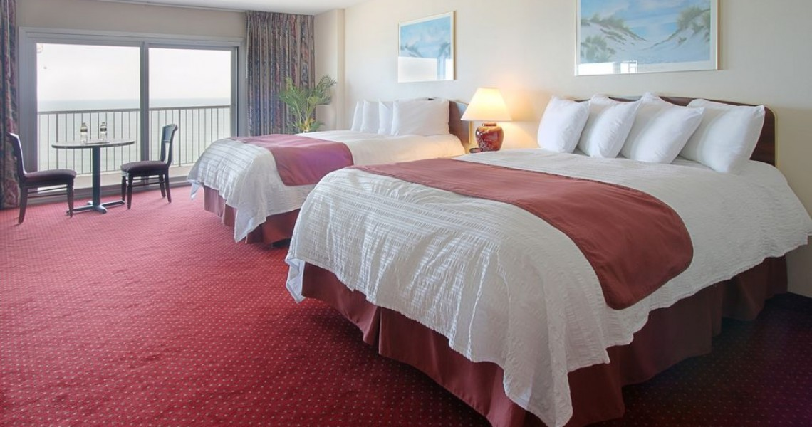 Two white queen beds in a red hotel room