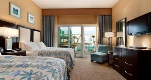 A suite with two queen sized beds and a glass door