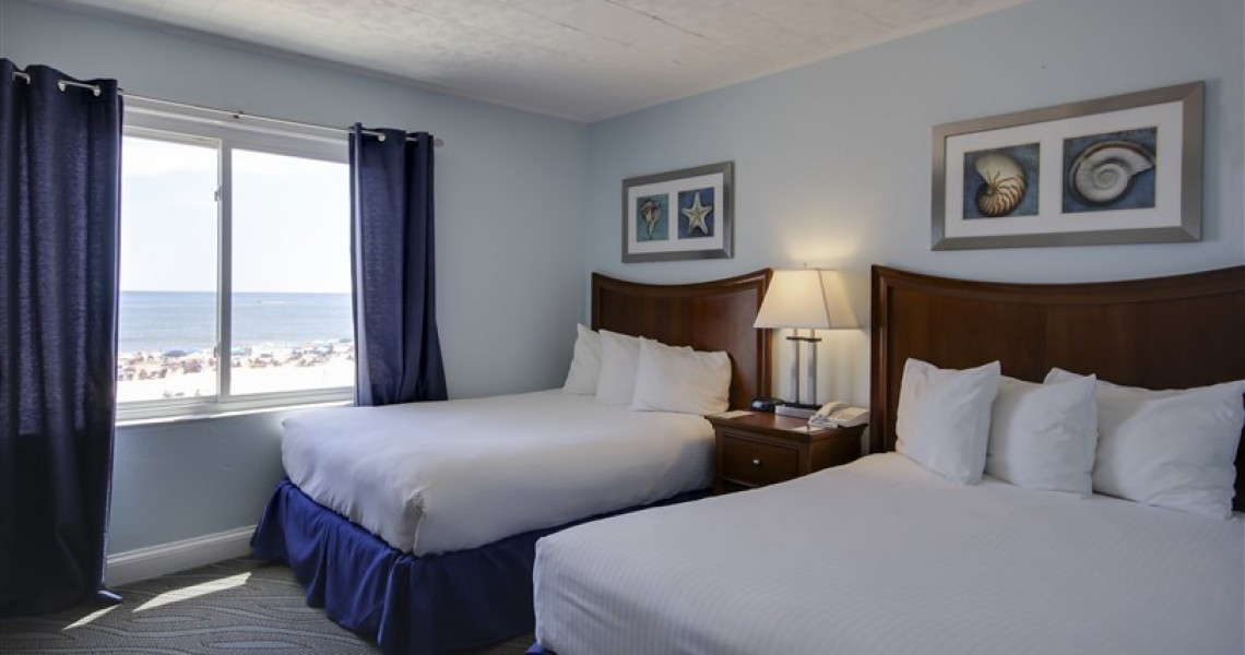 Two white queen sized beds overlooking the ocean