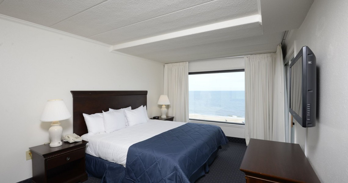 A single King Sized Bed with a window overlooking the ocean