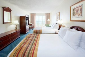 A bright hotel room with two queen beds