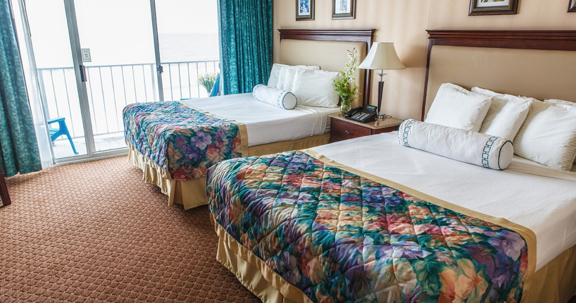 Two well maintained queen beds with a deck