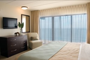 A cream colored King Sized bed overlooking the ocean