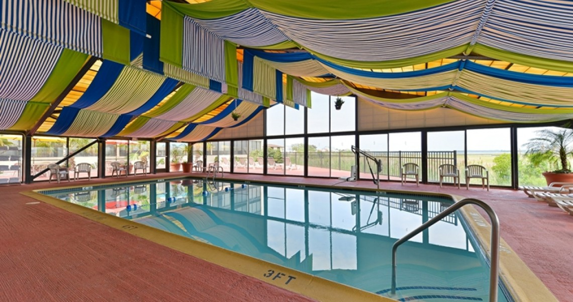 An enclosed pool with colorful sheets hung over the roof