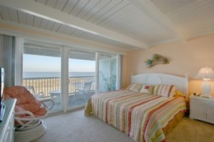 A view of the beach from a room with a colorful bed