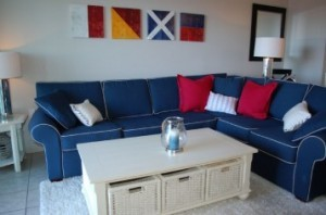 A wrap around blue couch with red and white pillows